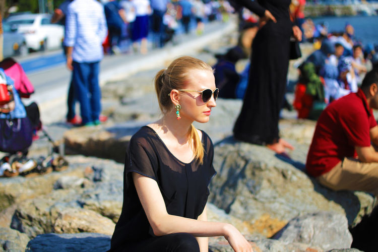 Young woman wearing sunglasses sitting on rock at beach during sunny day