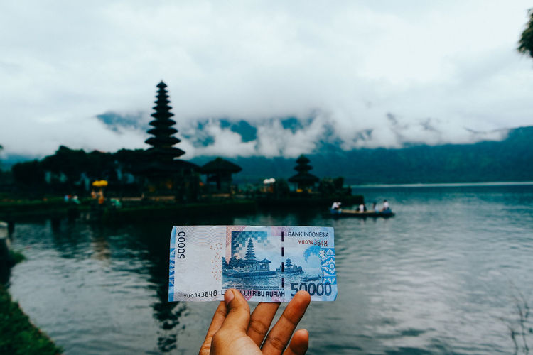 uang Rp.50.000 dengan latar Pura Ulun Danu Bratan. Human Hand Hand Water Human Body Part Holding One Person Sky Lake Real People Unrecognizable Person Personal Perspective Travel Destinations Focus On Foreground Lifestyles Outdoors Finger Body Part Money INDONESIA Bali Traveling Nature Cloud - Sky Day