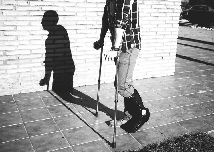 Low Section Of Injured Man Walking With Help Of Crutches On Sidewalk