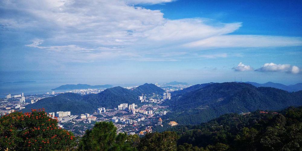 Panoramic view of townscape and mountains against sky