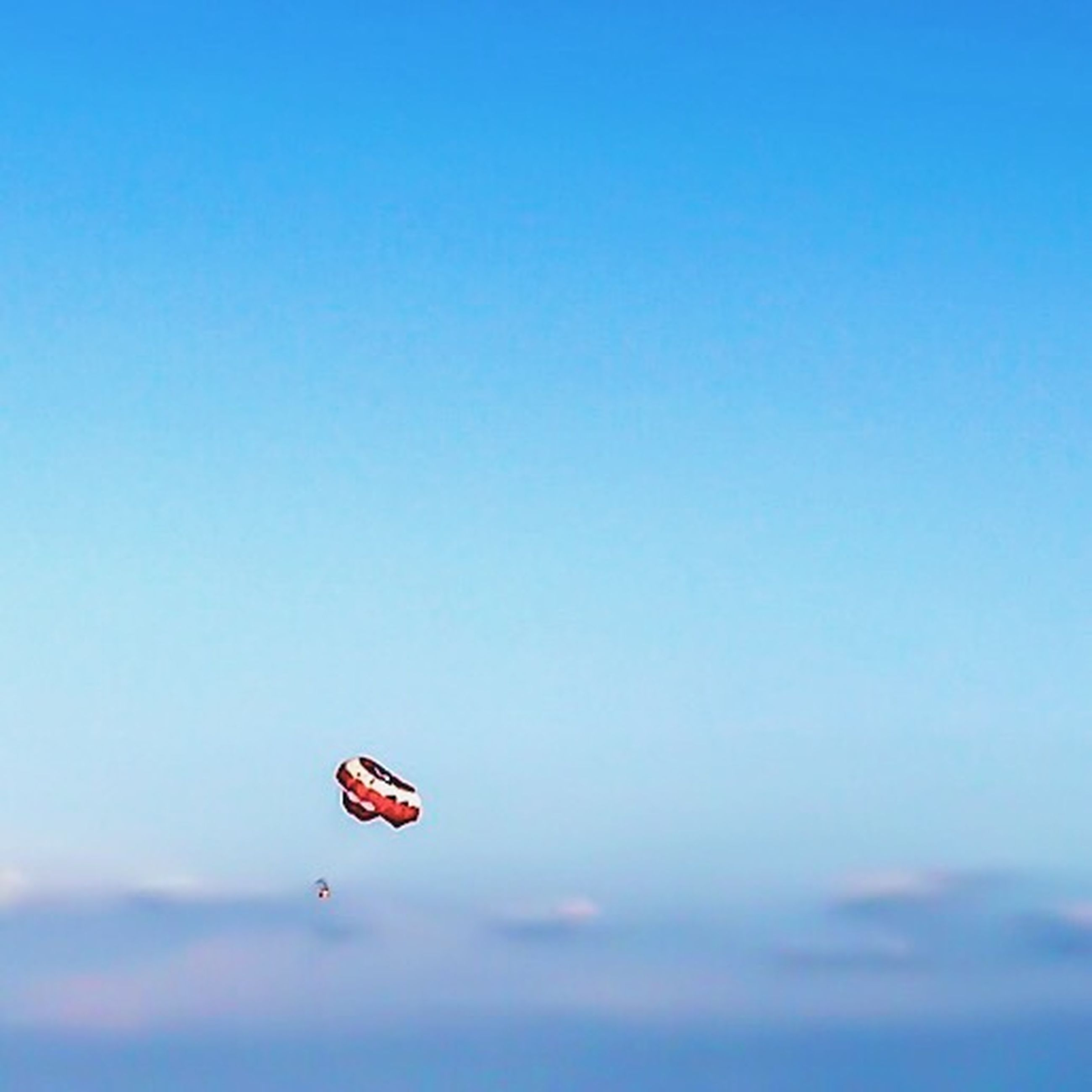 mid-air, flying, copy space, transportation, blue, low angle view, clear sky, adventure, sky, extreme sports, nature, parachute, motion, red, outdoors, day, beauty in nature, exhilaration, paragliding, insect