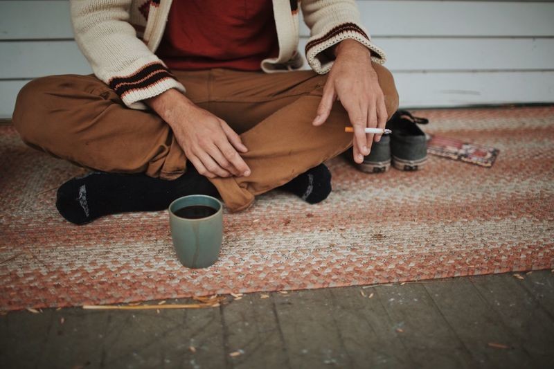 Low section of man holding cigarette while sitting by coffee mug at sidewalk