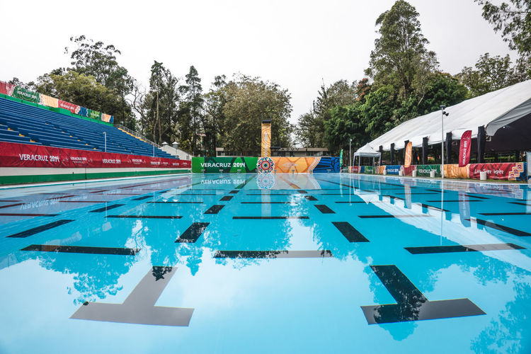 Abundance Arrangement Blue Day Empty Green Color Growth In A Row Low Angle View Multi Colored Nature No People Olympic Outdoors Pool Repetition Scenics Side By Side Sky Sports Sports Photography Sunny Swim Tilt Tree