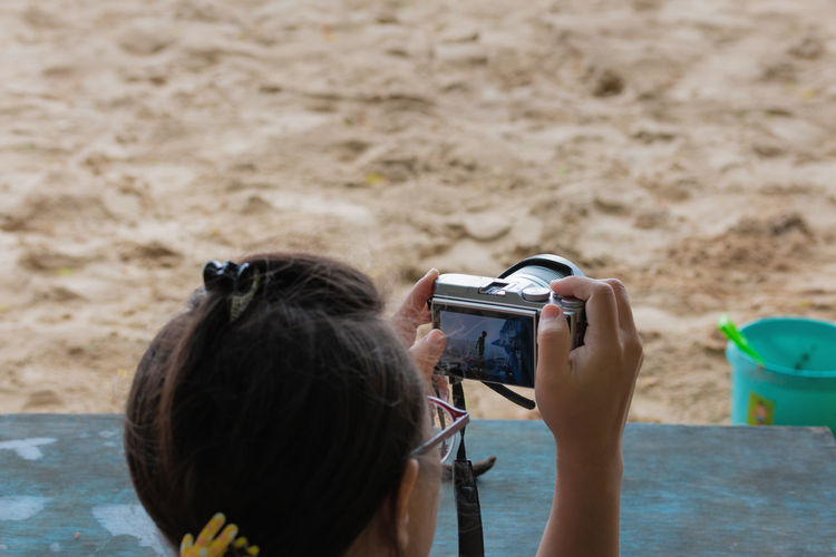 Rear view of woman photographing at beach