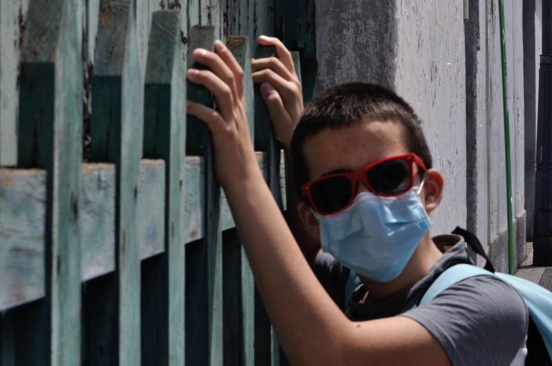 Portrait of boy wearing sunglasses standing by gate