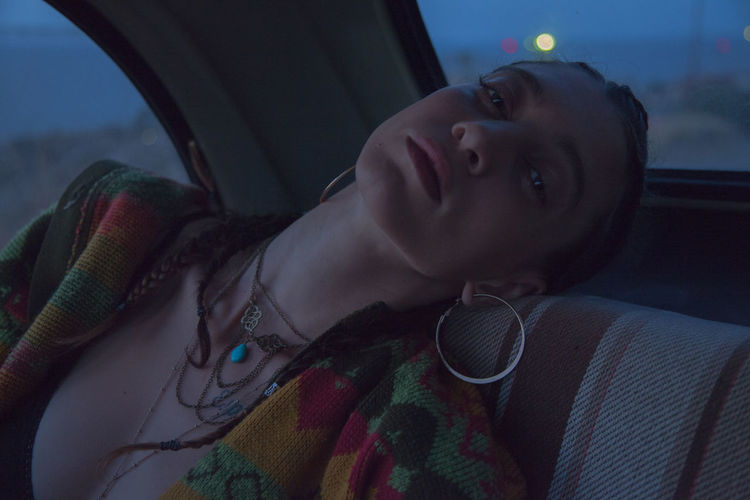 Portrait of young woman relaxing in car