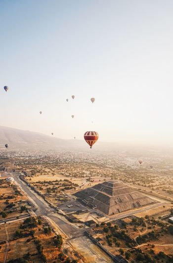 Aerial view of hot air balloons flying over landscape against sky