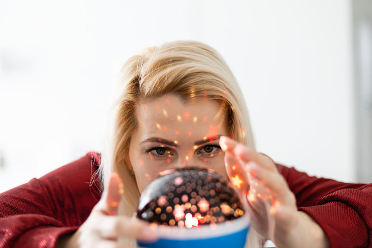 Close-up of woman holding illuminated lighting equipment