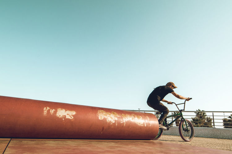 Side view of man riding bicycle against clear sky