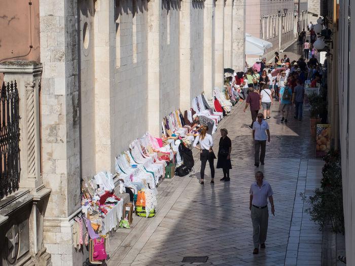 People walking on narrow street in city