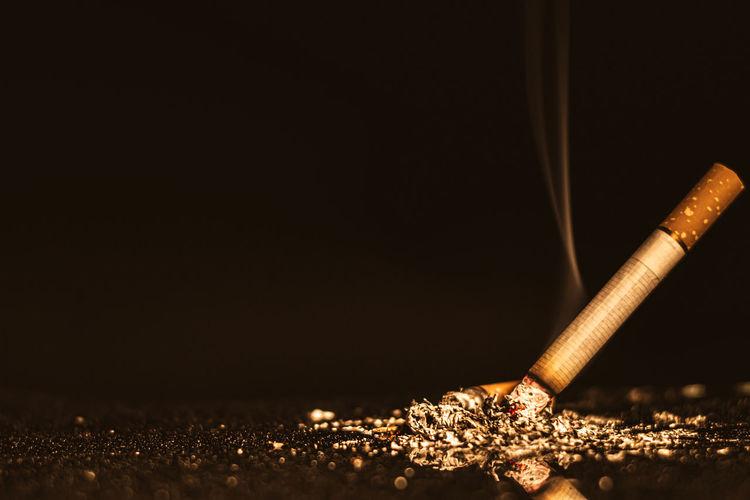 Close-up of illuminated cigarette against black background