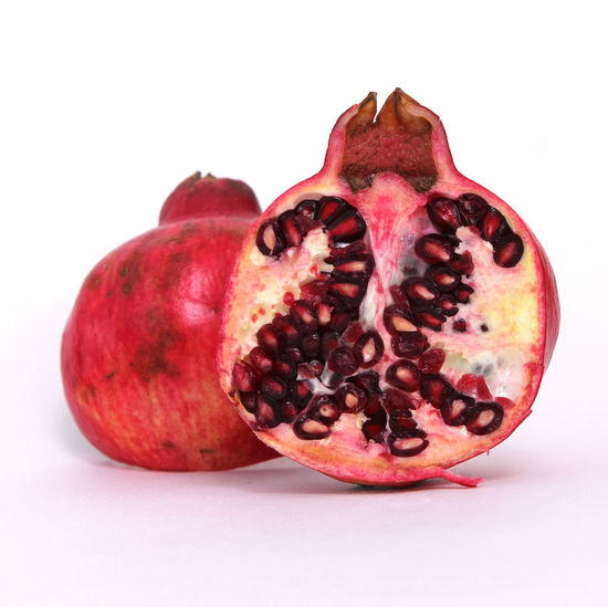 Food Food And Drink Studio Shot White Background Healthy Eating Pomegranate Fruit Wellbeing Seed Freshness Indoors  Close-up Cross Section No People Red Still Life Ripe Single Object Tropical Fruit Juicy