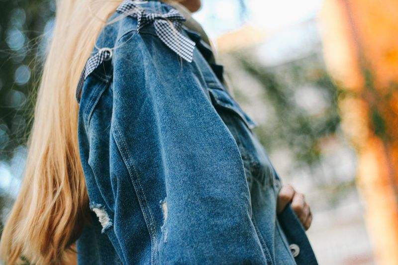 Midsection of woman wearing denim shirt outdoors
