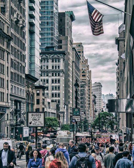 Crowd walking on city street against buildings