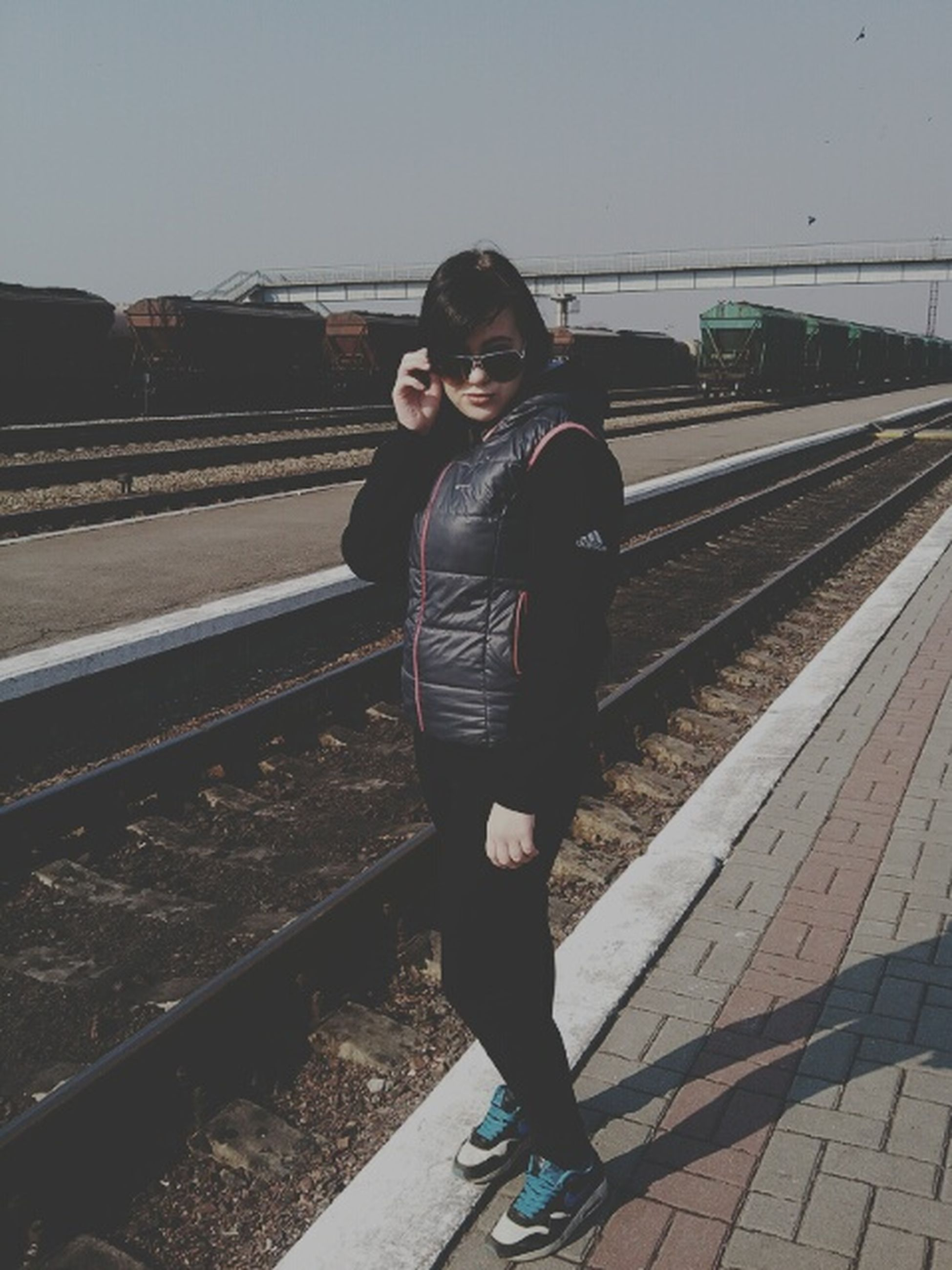 lifestyles, casual clothing, young adult, looking at camera, standing, railroad track, portrait, person, full length, front view, leisure activity, railing, young women, transportation, rail transportation, three quarter length, built structure, railroad station