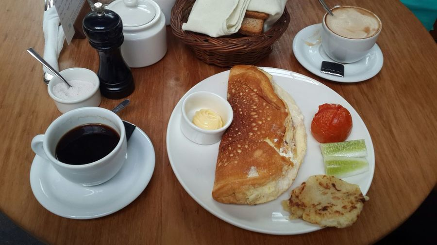 High Angle View Of Egg Omelet Served In Plate With Coffee Cup On Table