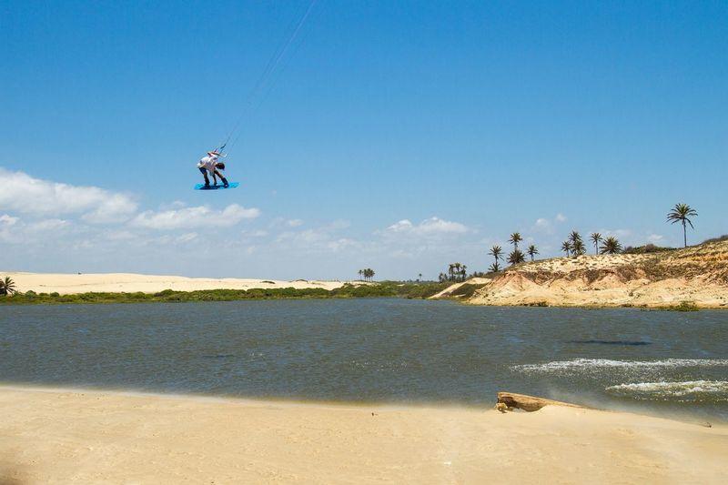 Man Kiteboarding In Sea Against Blue Sky