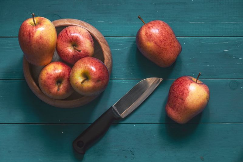 Red Apple Blue Light Wood Apple Fruit Apple Fruit Healthy Eating Food Food And Drink Wellbeing Freshness Indoors  Still Life Kitchen Knife Table No People Wood - Material Apple - Fruit High Angle View Knife Red Close-up Cutting Board