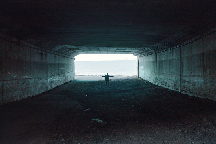 Rear View Of Man Standing In Tunnel Against Sea