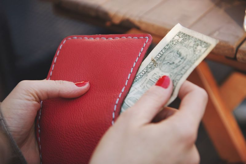 Close-up of woman removing paper currency from purse outdoors