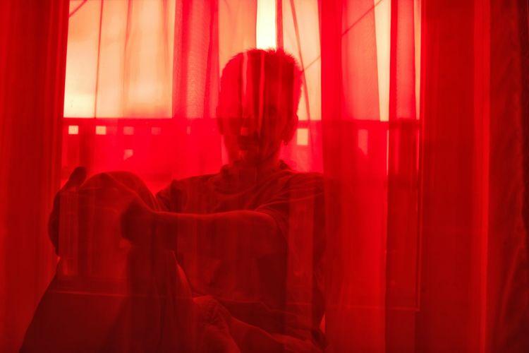 Man sitting behind red curtain