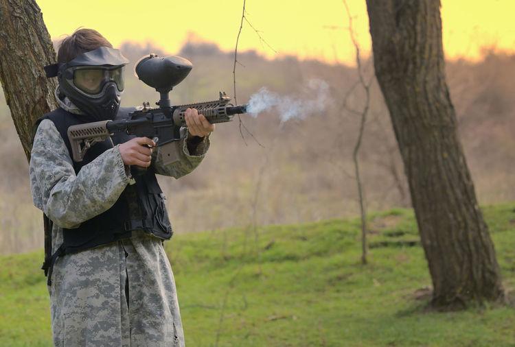Man Holding Gun On Field