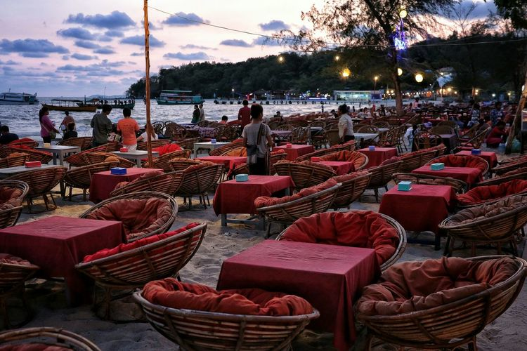 Empty chairs and tables at the shore