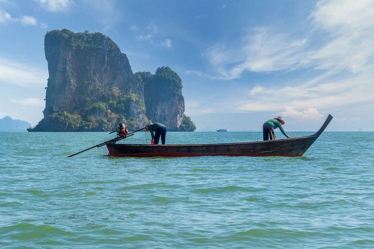 Fisherman fishing in sea against sky