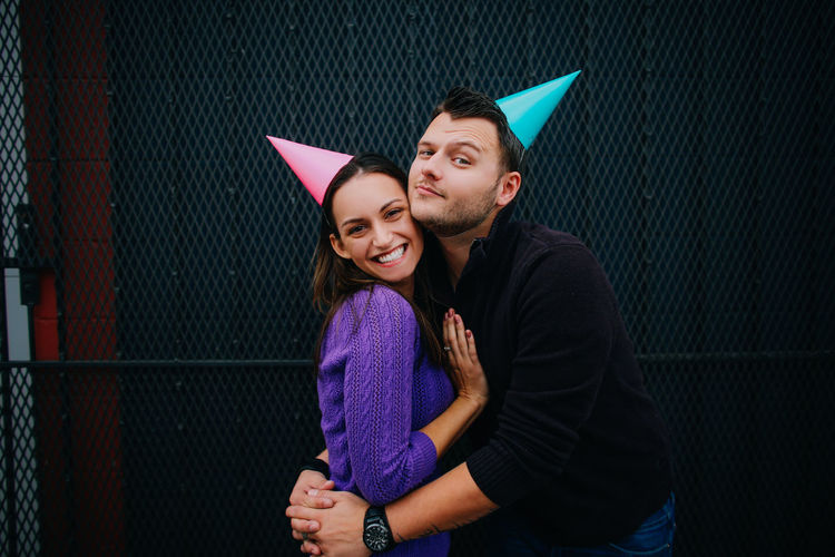 Portrait of man embracing woman while wearing party hats against metal grate