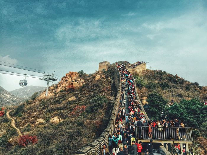 Tourists at great wall of china against blue sky