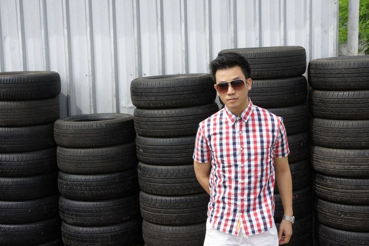 Portrait of man in sunglasses standing against tires
