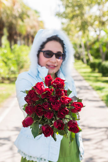 Woman wearing warm clothing holding bouquet