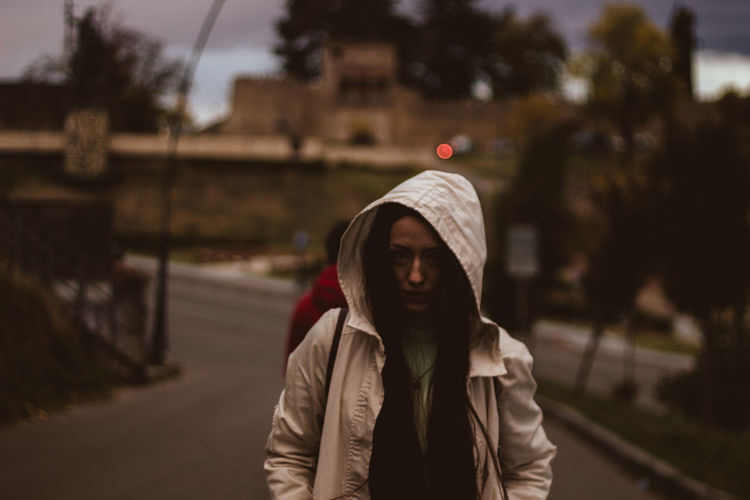Woman wearing hood shirt standing on road