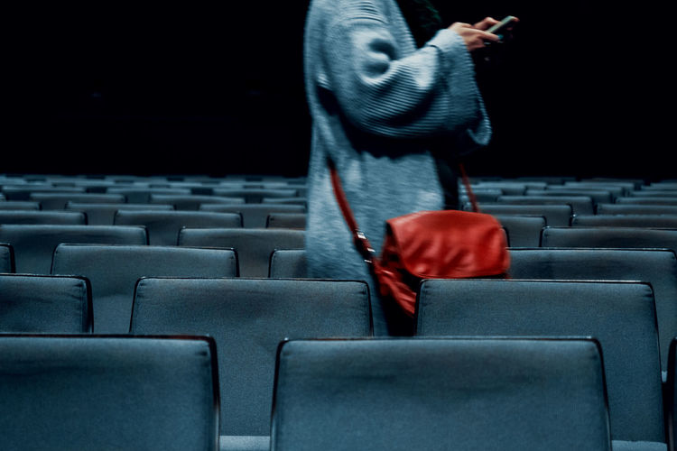 Midsection of woman using phone while standing in movie theater