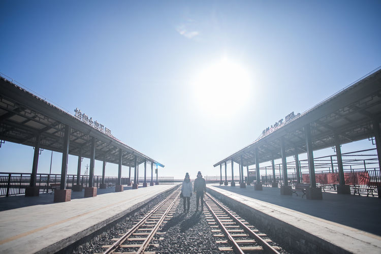 Sky Rail Transportation Sunlight Transportation Track Railroad Track Nature Architecture Day Sun Built Structure Direction The Way Forward Real People Sunny Clear Sky Railroad Station Platform Diminishing Perspective Travel Outdoors Lens Flare Bright