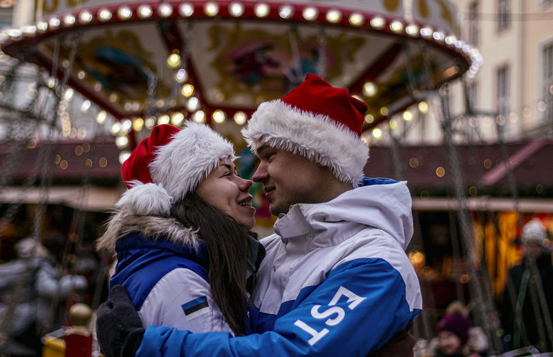 Portrait of young couple with carousel in amusement park