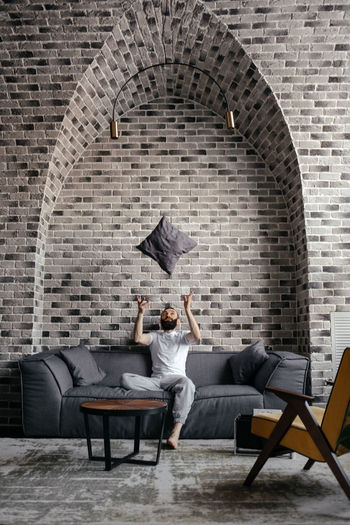 A man with a beard sitting on the sofa and throwing up a pillow