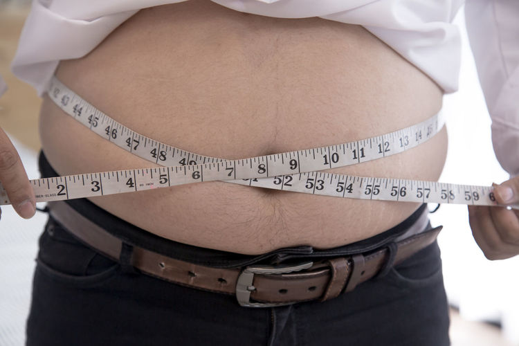 Midsection of overweight man measuring his stomach