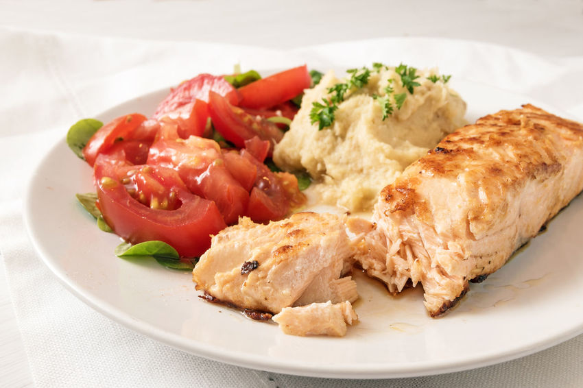 roasted salmon fillet with parsnip puree, tomato salad and parsley garnish, healthy diet meal on a white plate and blue napkin, high angle view from above, copy space Diet Puree Seafood Day Fish Food Freshness Healthy Eating Low Carb Mash Plate Ready-to-eat Roasted Salmon Serving Size Slimming Tomatoes Vegetable White