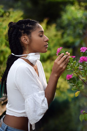 Side view of young woman holding flower bouquet