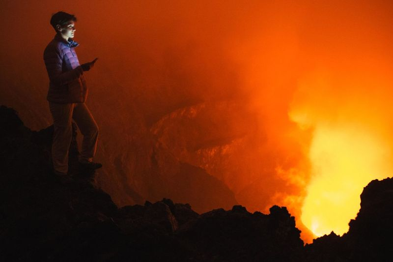 Full length of woman looking at volcanic eruption