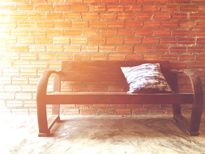 Couches sofa with pillows placed for the rest behind a brick wall background Brick Wall Brick Wall Seat Chair Architecture Wall - Building Feature No People Built Structure Relaxation Empty Absence Wood - Material Sunlight Stone Wall Building Exterior Bench Day Furniture