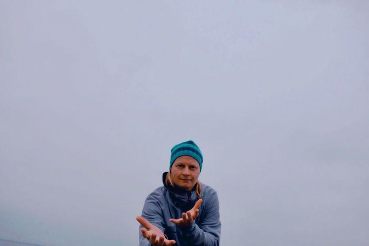 Portrait of man gesturing against sky