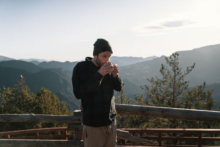 Man standing on railing against mountains drinking coffee