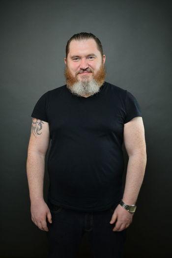 Portrait of mature man standing against black background