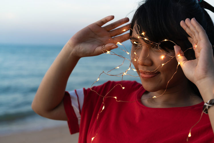 Woman with illuminated string lights looking away at beach