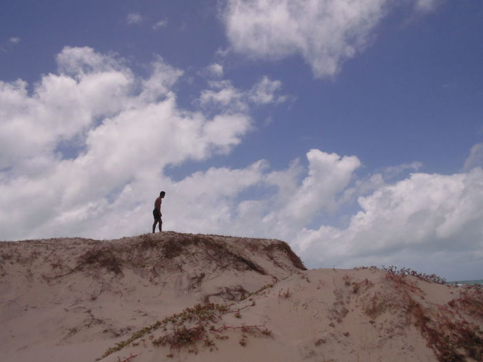 Man Standing On Sand Dune At Desert Against Sky