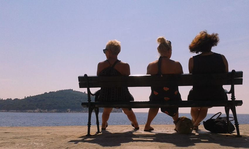 Togetherness Adults Only Women Sitting Friendship Young Women People Outdoors Beach Leisure Activity Only Women Group Of People Sky Day Adult Women Sitting Sitting On A Bench Contemplating Beauty Contemplation Ocean Sea And Sky Seaside Friends Female Friends