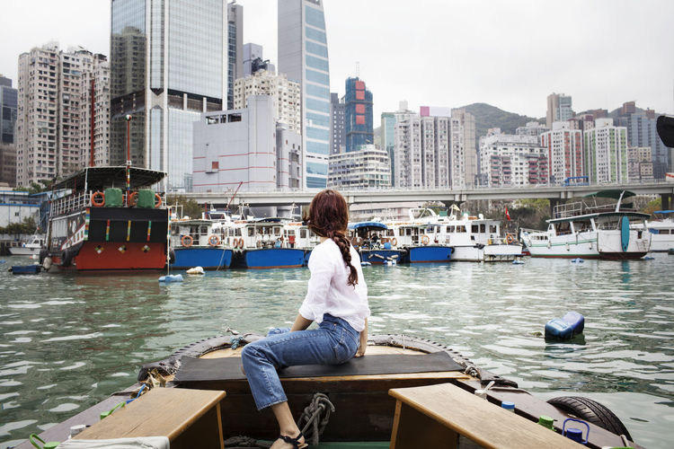 Man sitting on boat against buildings in city