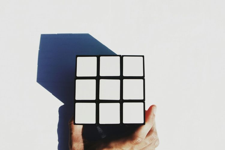 Cropped Hand Holding Puzzle Cube Against White Background